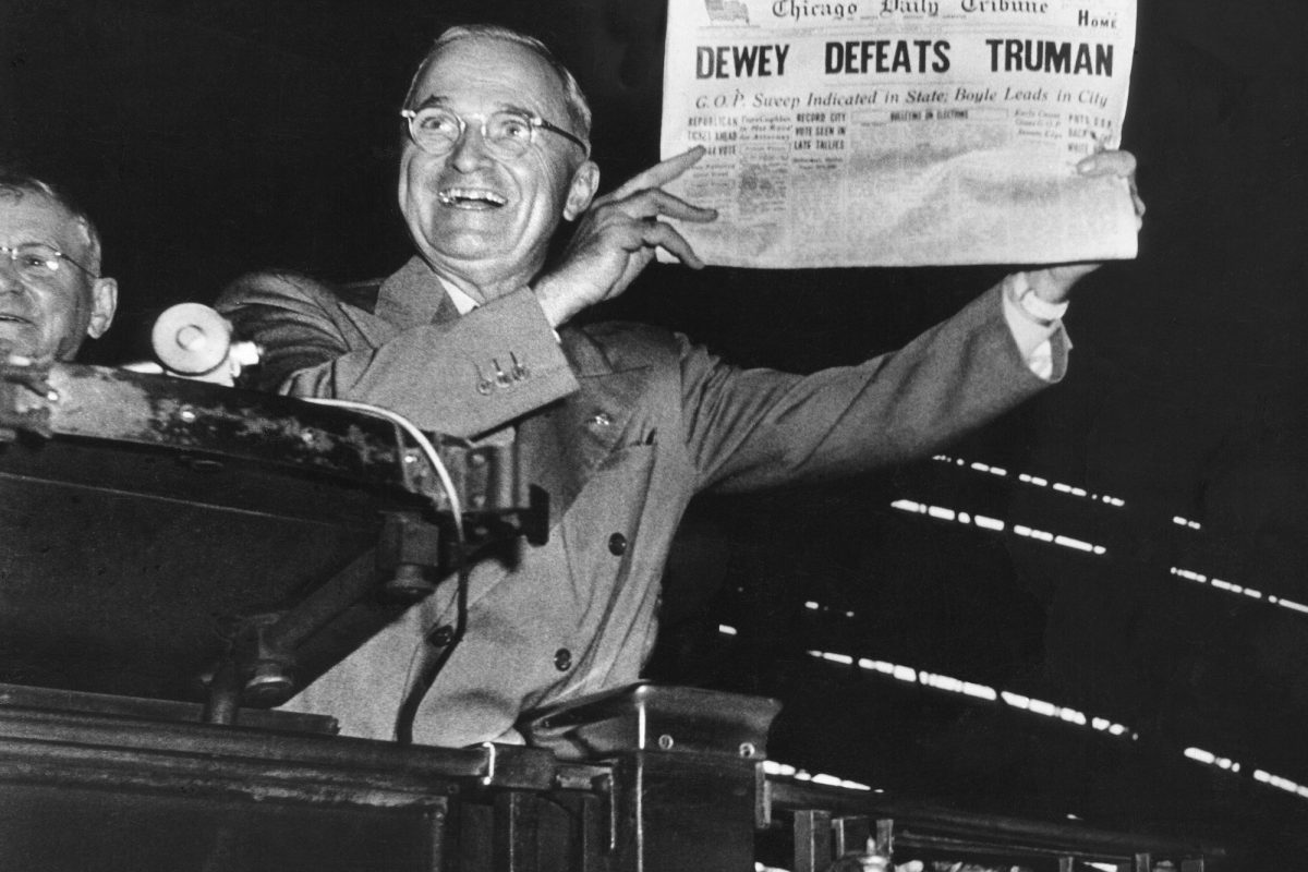 Victorious presidential candidate Pres. Harry Truman jubilantly displaying erroneous CHICAGO DAILY TRIBUNE w. headline DEWEY DEFEATS TRUMAN which overconfident Republican editors had rushed to print on election night, standing on his campaign train platform.  (Photo by W. Eugene Smith/The LIFE Picture Collection/Getty Images)